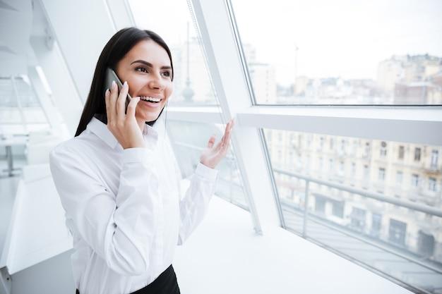 Donna d'affari che parla al telefono e sta in piedi vicino alla finestra
