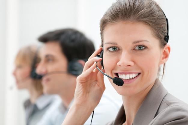 Donna d'affari e team che lavora al call center