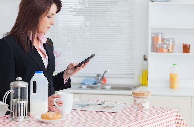 Invio di messaggi di testo della donna di affari mentre mangiando prima colazione in cucina