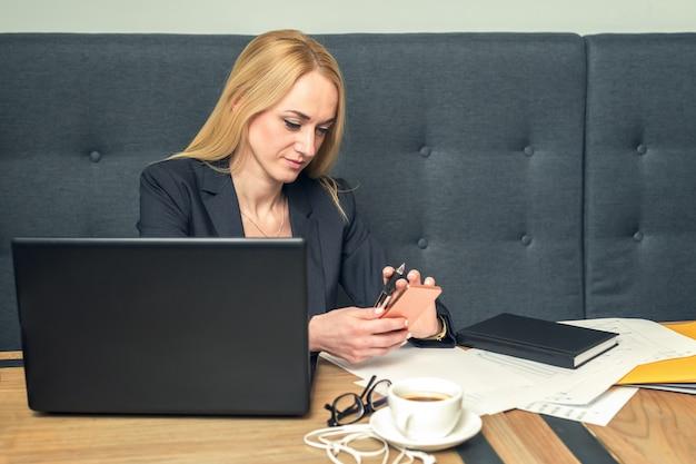 Donna di affari che manda un sms sul telefono e che lavora al computer portatile all'ufficio.