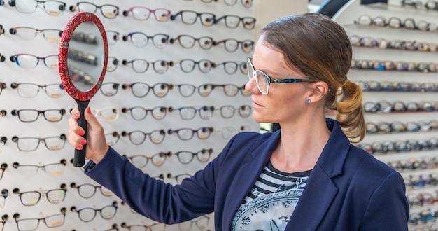 La donna di affari prova i vetri davanti ad uno specchio in un negozio di ottica