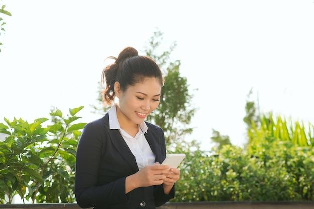 La donna d'affari usa lo smartphone al parco giardino