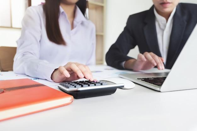 La donna di affari che utilizza la calcolatrice per calcolare il consulente descrive un piano di marketing per impostare le strategie di business per gli imprenditori. pianificazione del budget aziendale e concetto di ricerca.