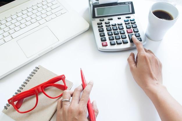 Donna di affari che utilizza calcolatrice e computer portatile sulla scrivania bianca, concetto di contabilità con copia spazio