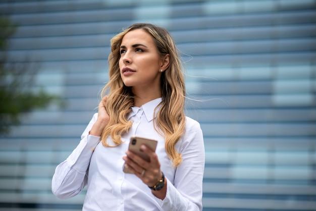Donna d'affari utilizzando il suo telefono cellulare davanti al suo edificio per uffici