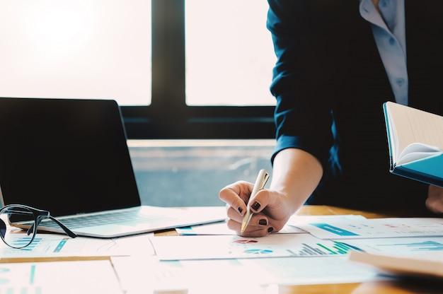 La donna di affari che utilizza il computer portatile per fa la matematica di finanza sullo scrittorio di legno nell'ufficio e nel fondo di lavoro di affari, tasse, contabilità, statistiche e concetto di ricerca analitica