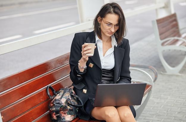 Una donna d'affari utilizzando un computer portatile mentre era seduto in una strada frondosa della città moderna
