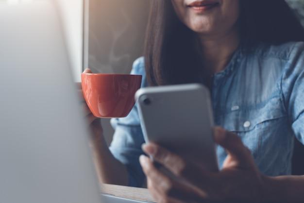 Donna d'affari utilizzando smartphone mobile e bere caffè