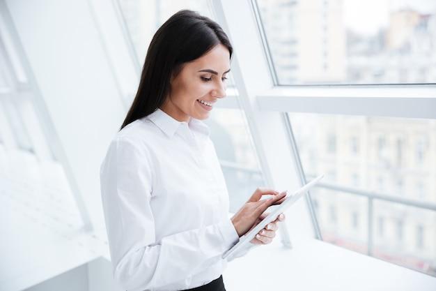 Donna d'affari che utilizza computer tablet e in piedi vicino alla finestra in ufficio