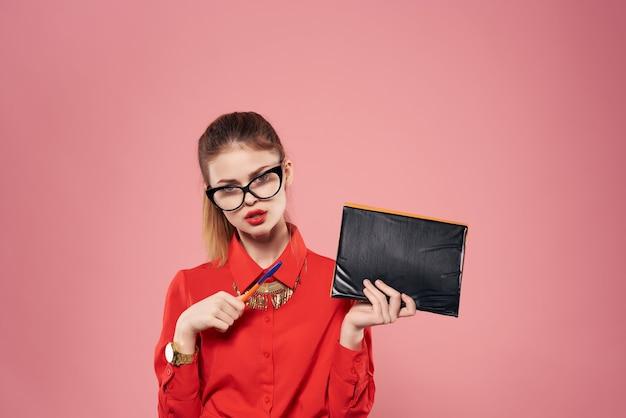 Posa professionale del segretario del blocco note della camicia rossa di occhiali da portare della donna di affari. foto di alta qualità
