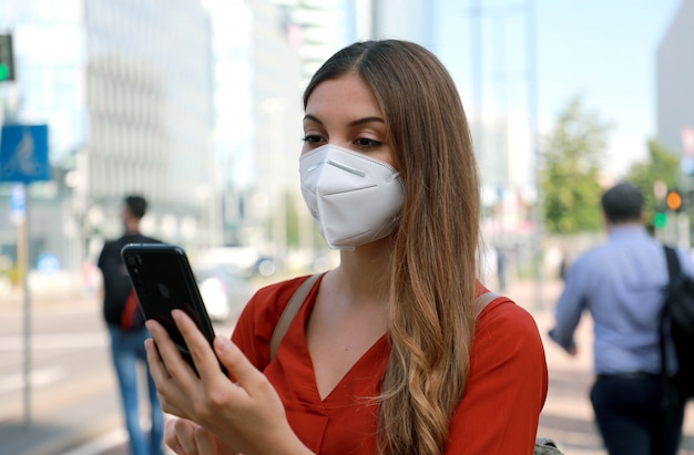 Donna di affari che indossa la maschera facciale kn95 ffp2 che cammina nella strada della città moderna che tiene uno smartphone