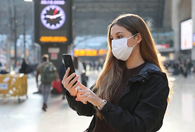 Donna d'affari che indossa una maschera protettiva acquisto di biglietti online con app per smartphone alla stazione ferroviaria