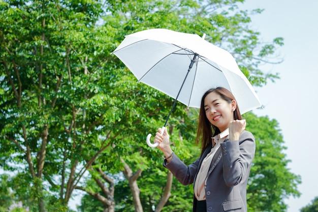 Una donna d'affari che indossa un abito, tiene in mano un ombrello bianco ombreggiato dal sole. e ha alzato una mano felice per lavorare con successo