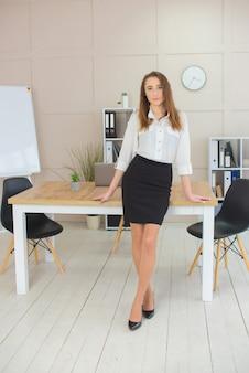 Donna d'affari in una camicetta bianca con un sorriso seduto al tavolo nel suo ufficio.