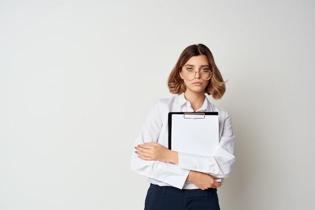 La donna d'affari con i documenti della camicia bianca lavora su uno sfondo chiaro