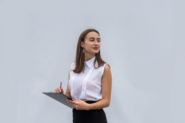 Donna d'affari in camicia bianca che tiene il documento negli appunti, isolato su uno sfondo bianco.