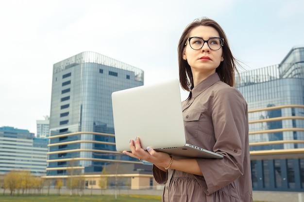 Donna d'affari con il computer sullo sfondo di un moderno edificio aziendale.