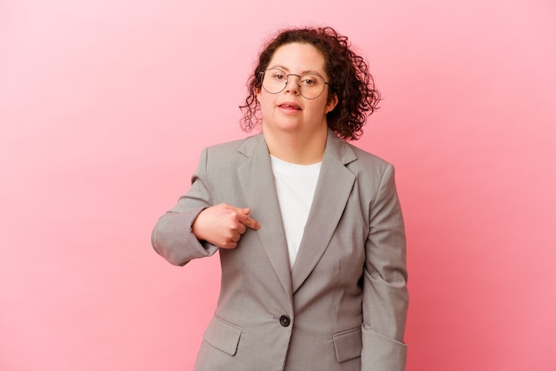 Donna di affari con sindrome di down isolata sulla persona del muro rosa che indica a mano uno spazio della copia della camicia, orgoglioso e fiducioso