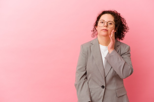 La donna di affari con la sindrome di down sul rosa sta dicendo una notizia segreta di frenata calda e sta guardando da parte