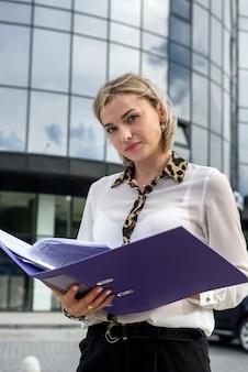 Donna d'affari con in piedi piegato davanti all'edificio per uffici e guardando a porte chiuse
