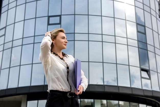 Donna d'affari con cartella in piedi fuori dall'edificio degli uffici Foto Premium
