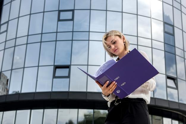Donna d'affari con cartella in piedi fuori dall'edificio degli uffici