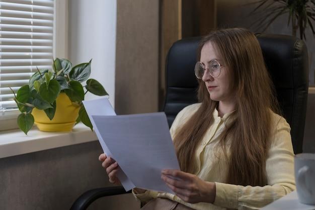 La donna d'affari con gli occhiali sta studiando seriamente i documenti. esamina il contratto prima di concludere un accordo.