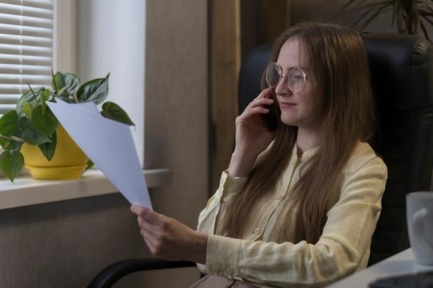La donna d'affari con gli occhiali sta studiando seriamente i documenti. esamina il contratto prima di fare un affare