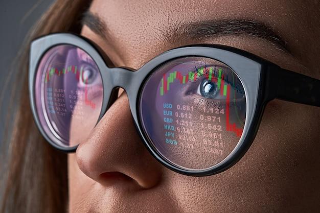 La donna di affari con gli occhiali esamina le quotazioni del mercato azionario e i tassi di cambio durante la crisi finanziaria