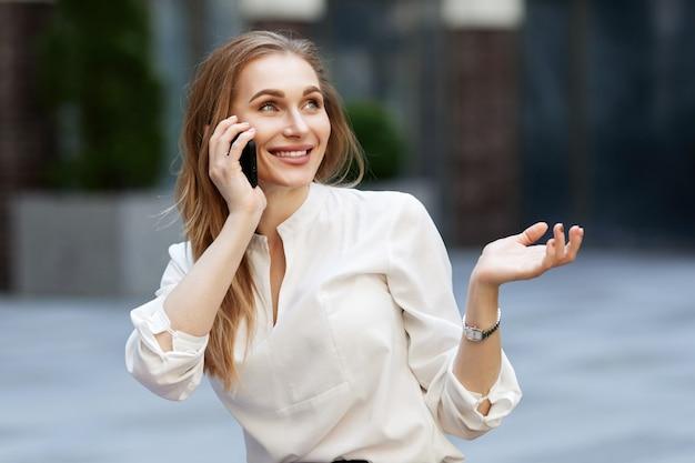 Donna d'affari con gli occhiali che parla al telefono