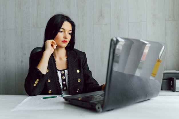 Donna d'affari con il suo staff, gruppo di persone in background in ufficio moderno e luminoso al chiuso