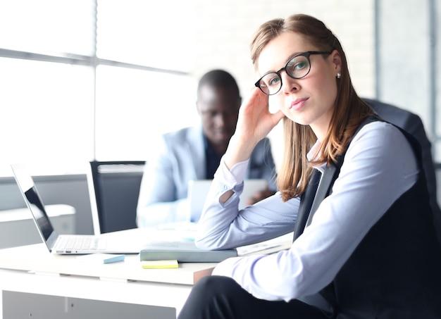 Donna d'affari con il suo personale, gruppo di persone in background in un moderno ufficio luminoso al chiuso.