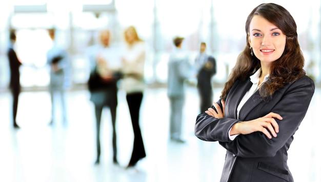 Donna d'affari con il suo personale, gruppo di persone presso l'ufficio moderno e luminoso al chiuso