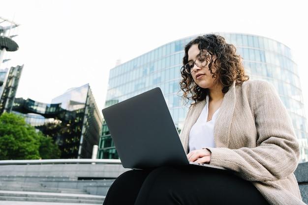 Donna di affari con il computer portatile che si siede sulle scale all'aperto un moderno centro ufficio o una banca.