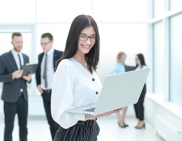 Donna d'affari con laptop in piedi nella hall della banca