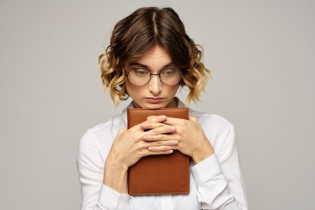 Donna d'affari con blocco note e occhiali su una luce