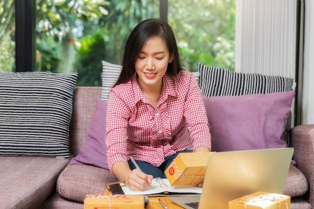 Donna d'affari con vendite online e spedizione di pacchi nel suo ufficio a casa