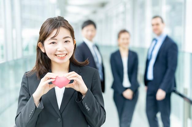 Donna d'affari con un piccolo cuscino a forma di cuore e la sua squadra