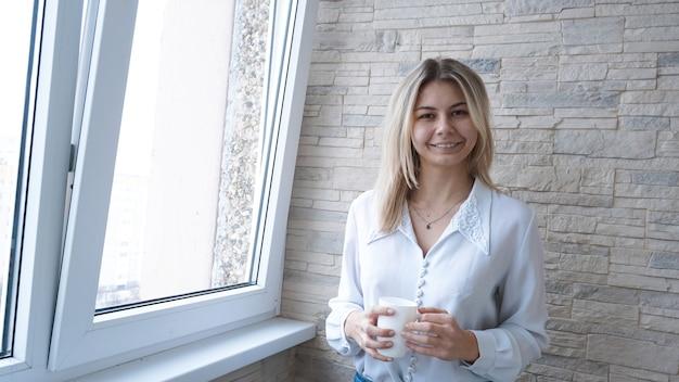 Donna d'affari con una tazza di caffè bianca che guarda fuori dalla finestra - muro di mattoni