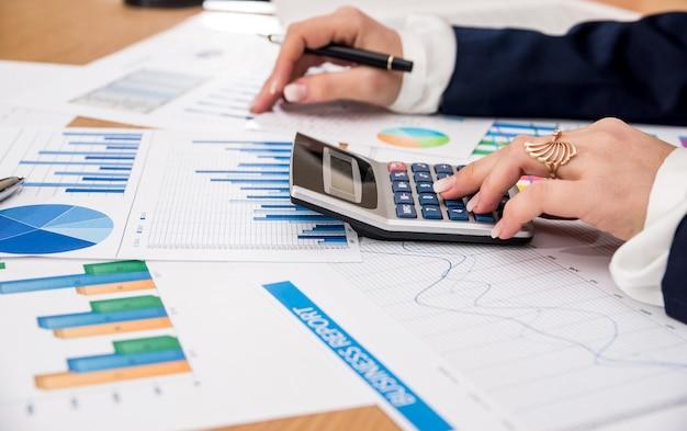 Donna di affari che lavora al grafico commerciale con la calcolatrice