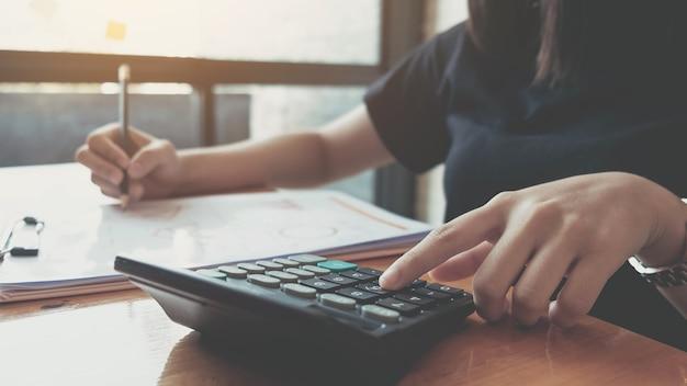 Donna d'affari che lavora nel settore finanziario e contabile analizza il budget finanziario con la calcolatrice e il computer portatile in ufficio
