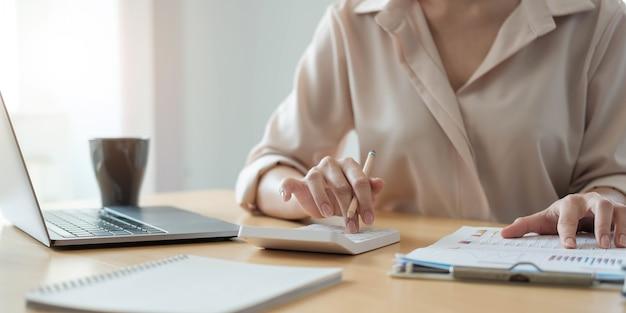 Donna d'affari che lavora in finanza e contabilità analizza il budget finanziario con calcolatrice e computer portatile in ufficio