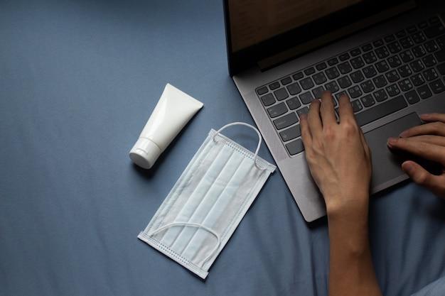 La donna di affari che lavora dalla casa e l'alcool gel per le mani e la maschera accanto al taccuino del computer
