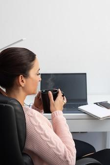 Donna d'affari che lavora al computer portatile a casa, seduta alla scrivania bevendo un tè caldo - copia spazio.