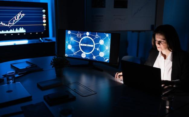 Donna d'affari che lavora di notte all'interno dell'ufficio della società fintech facendo ricerca blockchain