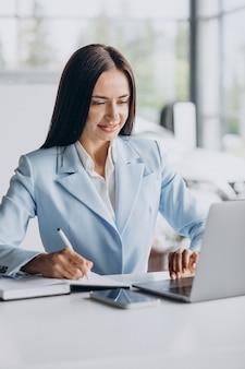Donna d'affari che lavora in ufficio al computer