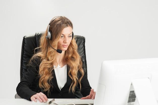 Donna d'affari che lavora in ufficio usando con l'auricolare