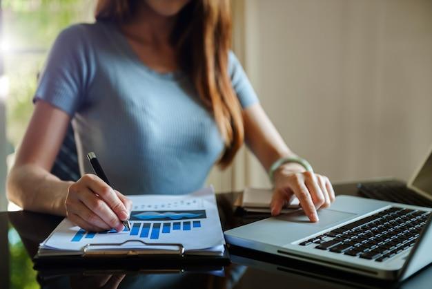 Donna d'affari che lavora in ufficio con laptop e documenti sulla sua scrivania nuovo progetto di avvio. compito finanziario.