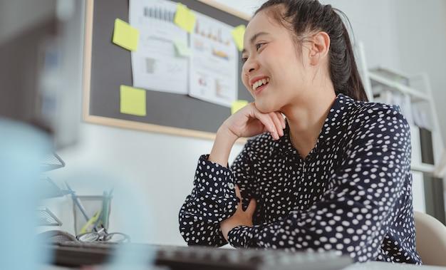 Donna d'affari che lavora e si siede alla scrivania in ufficio mettendosi il mento sulle mani e sorridendo