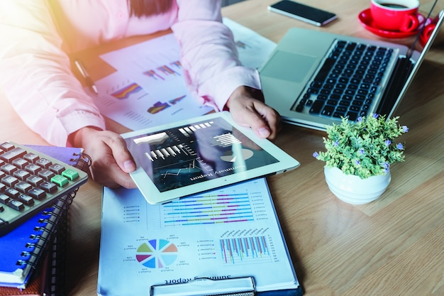 Donna di affari che lavora con la compressa digitale e libro e documento sullo scrittorio di legno in moderno